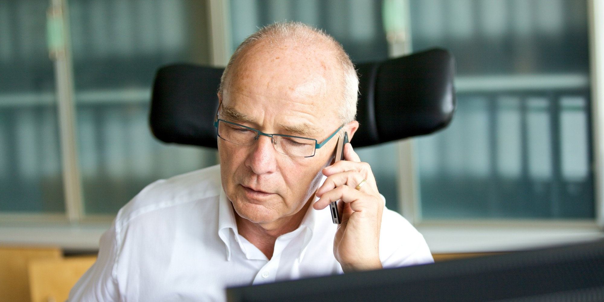 Senior man on cell phone in home office