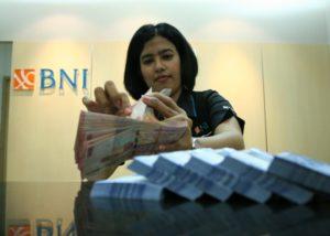 Teller Bank BNI menghitung uang. (Tempo/Adri)